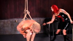 Red-haired domme whips a tied and suspended slave in bondage