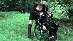 Busty mistress in leathers tortures a handicapped dude in latex